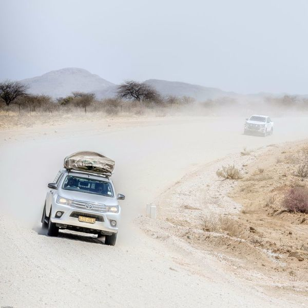 Cars on a dusty desert road in Namibia